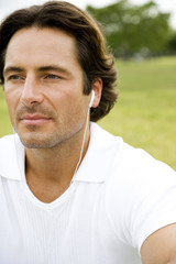 Portrait man with earphones sitting in the park