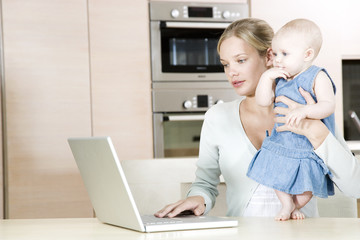 Mother using a laptop in the  kitchen at home, holding baby daughter