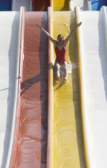 A woman coming down a slide in a waterpark