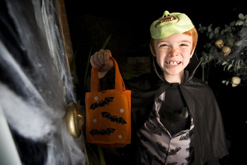 Boy in costume at a Hallowe'en party, holding an orange party bag