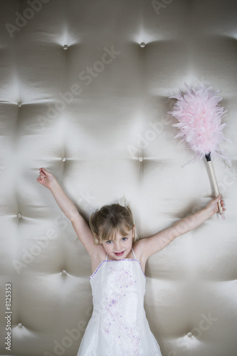 Little girl in a party dress holding a pink feather duster