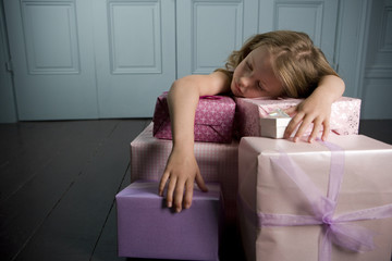 Young girl asleep and laying on her with birthday presents
