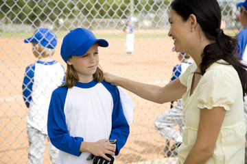 Mother encouraging daughter at little league baseball game