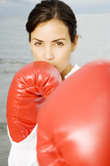 A woman wearing boxing gloves on a beach