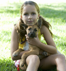 Young girl sitting in the garden holding a puppy
