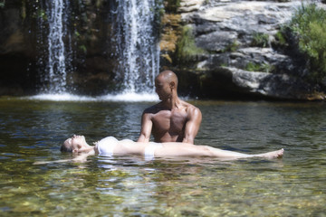 Young couple in a natural pool near a waterfall