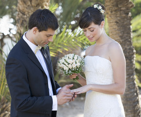 A groom placing the ring on his bride