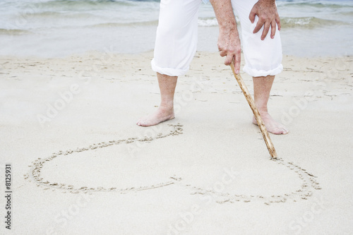 Senior man drawing a heart shape in the sand, close up