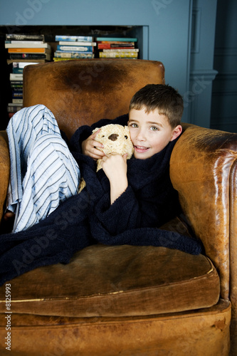 Little boy sitting in armchair with teddy bear