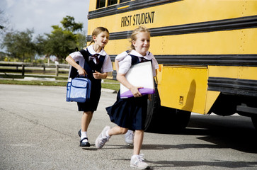 Two schoolgirls running for the school bus
