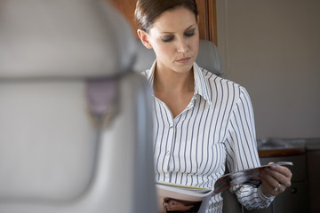 A passenger reading a magazine on a flight