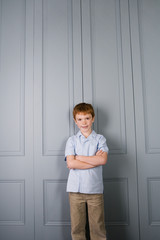 boy standing against very tall door