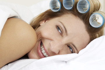 Young woman laying in bed with curlers in hair