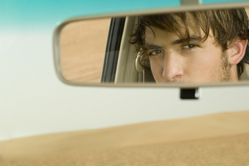 A young man's reflection in a rear view mirror