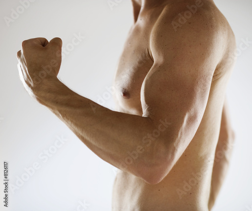 A male nude, flexing bicep muscles