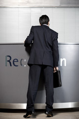 Businessman waiting at office reception, waiting for the receptionist to return