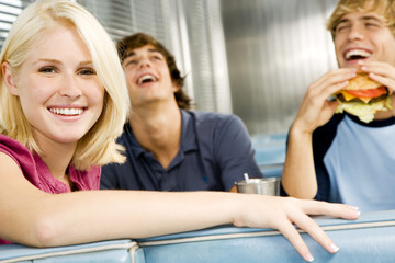 Portrait of a smiling teenage girl with her friends in a diner