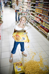 Naughty young girl emptying cereal over a supermarket floor
