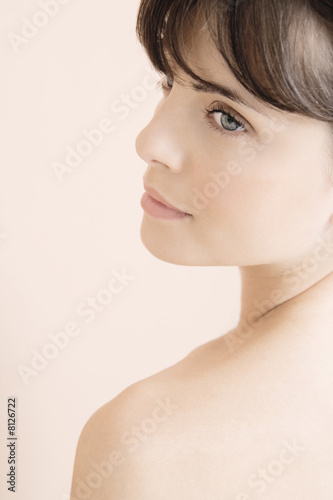 Portrait of young woman looking over her shoulder