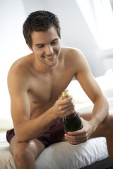 Young man opening a bottle of champagne in the bedroom