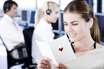 Businesswoman reading her valentines card in an office