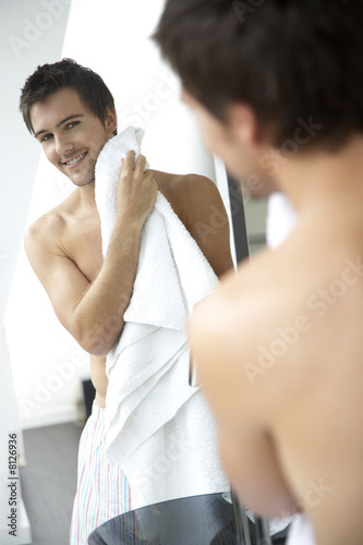 Young man drying his face with a towel
