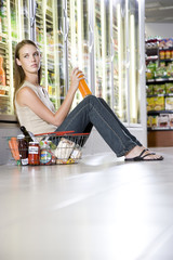 Woman sitting on a supermarket floor drinking.