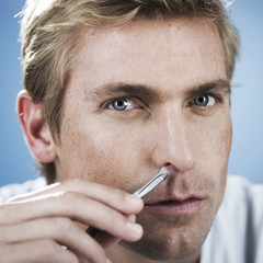 A young man using tweezers to pluck nasal hair