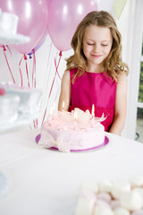 little girl looking down at birthday cake