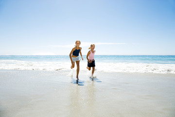 Two young girls running on the beach
