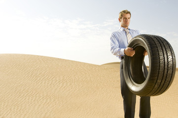 A man standing in the desert with a tyre