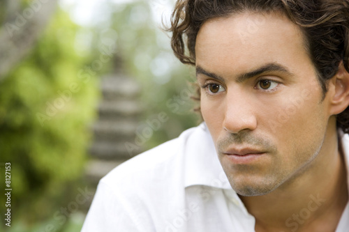 Portrait of a serious looking man in a tropical garden.