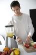 Young man preparing fresh fruit juice