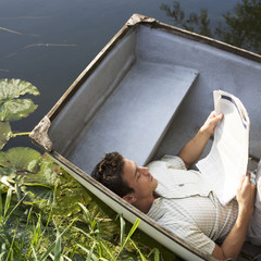Young man laying in a boat reading a newspaper