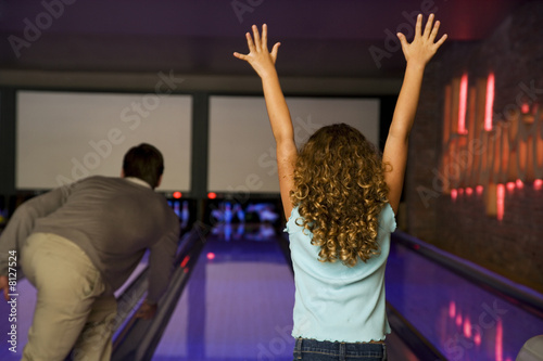 Father and daughter in a bowling alley, celebrating victory