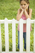 sad little girl leaning on fence