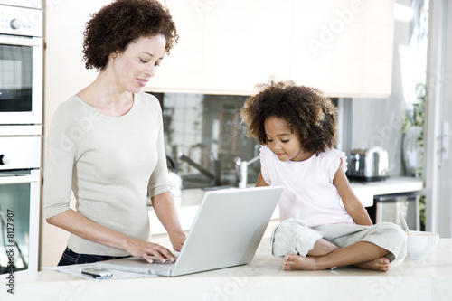 Mother using a laptop in the kitchen at home, while young daughter looks on