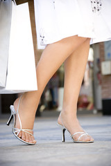 Woman holding shopping bags in the street, close-up of legs