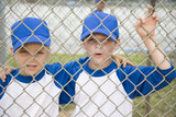 two boys hugging looking through fence