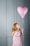 little girl in party dress looking at her pink heart shaped balloon