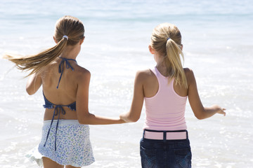 Two young girls running on the beach hand in hand