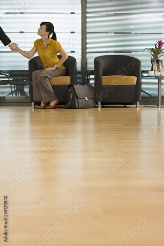 Businesswoman sitting in office reception area, shaking hands with businessman, surface level
