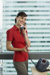 Businesswoman in red short-sleeved blouse using telephone in office, standing beside window