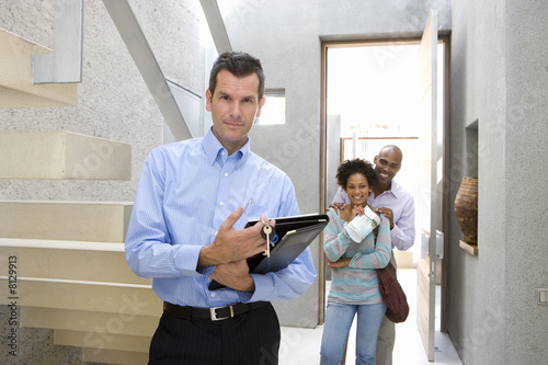 Male real estate agent standing by stairs, couple embracing in background, smiling, portrait
