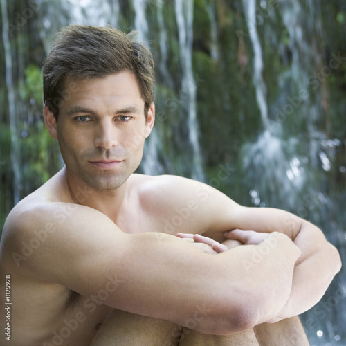 A man sitting by a waterfall
