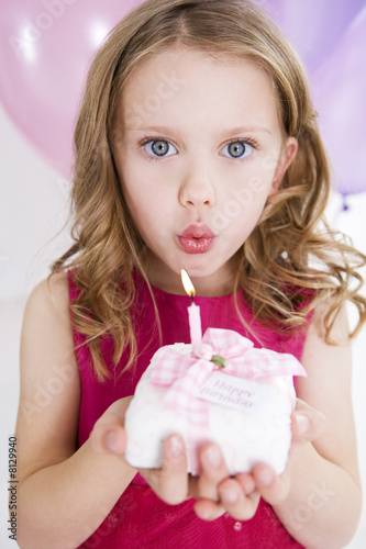 little girl blowing out candle on miniature birthday cake