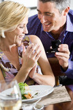 Mature man proposing to mature woman at dinner table, smiling, woman looking at engagement ring