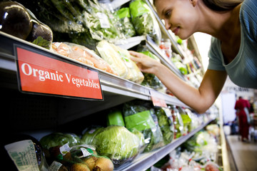 Woman reading the label on an organic food packaging in a supermarket