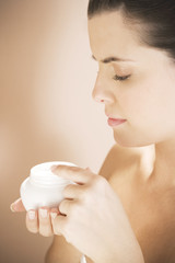 Woman holding a pot of moisturising cream