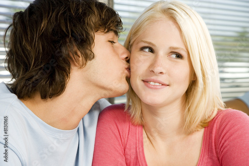 Portrait of a teenage couple with the boy kissing the girl